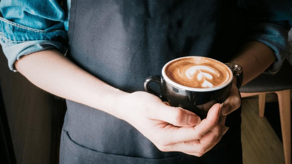 Persoon in chefsoutfit houdt een warme kopje koffie vast en heeft een horloge aan.