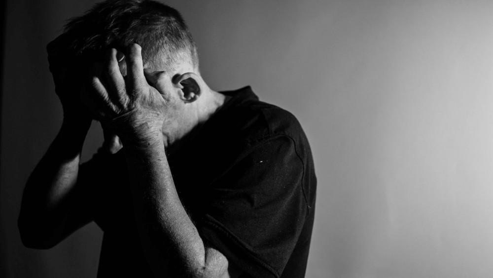 Man met zwart t-shirt met de handen op het hoofd in zwart-wit foto.