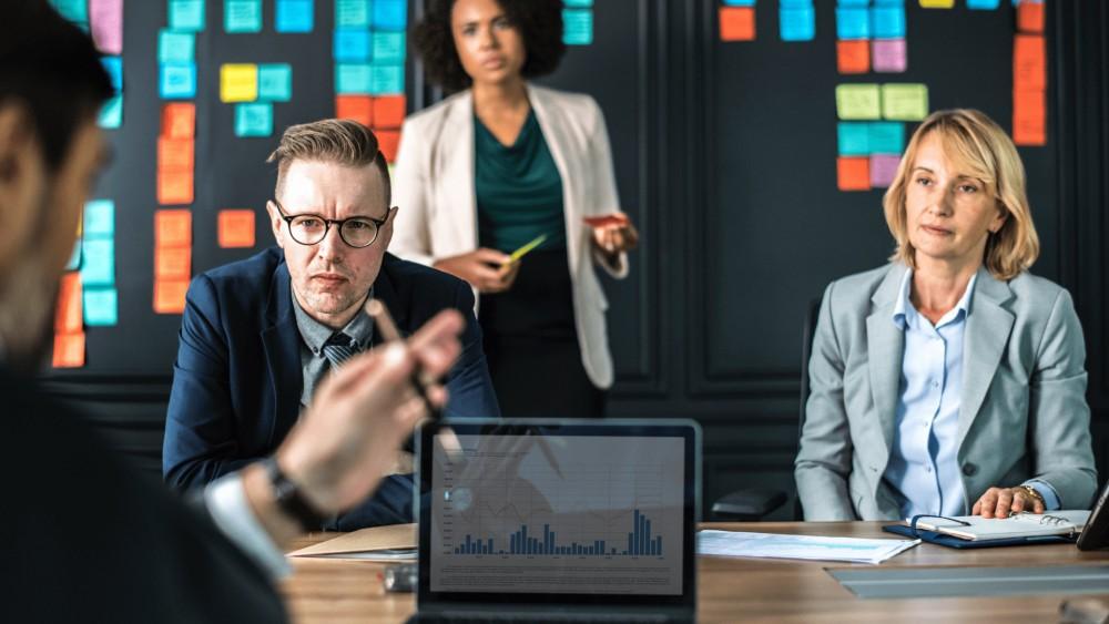 Een groep experts en consultants in formele kledij met brainstorm materiaal zoals postits en een muur voor notities op de achtergrond met laptop in de voorgrond met statistijken en bedrijfscijfers voor het financieel plan en het business plan.
