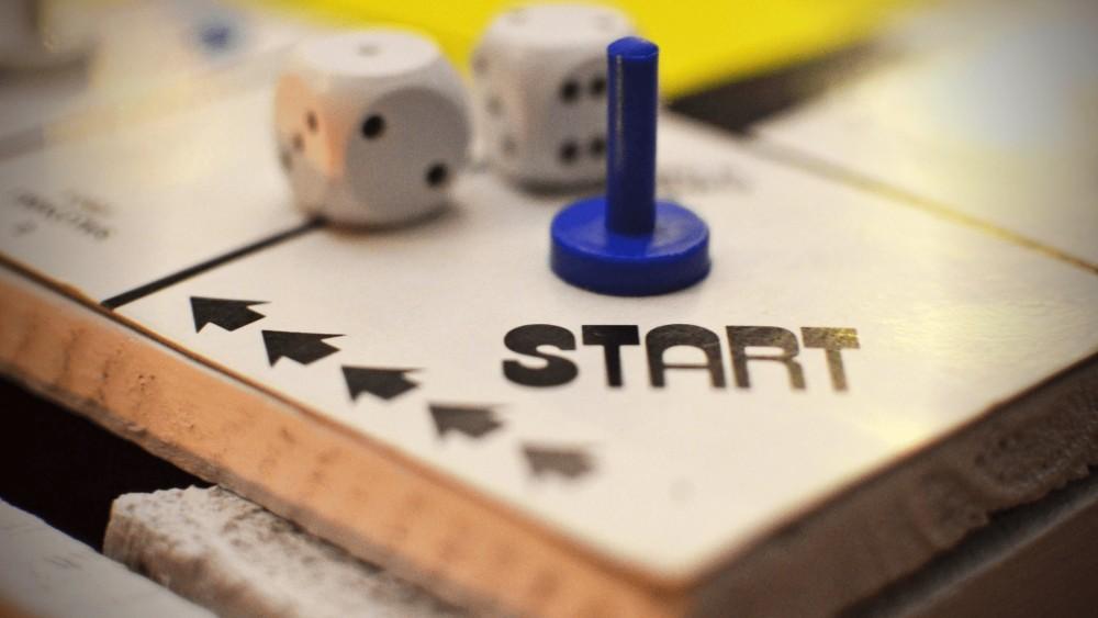 Een monopolie-bord (board game) met daarop twee dobbelstenen en één pion, met het start-logo van monopolie in beeld en het bord op de achtergrond.