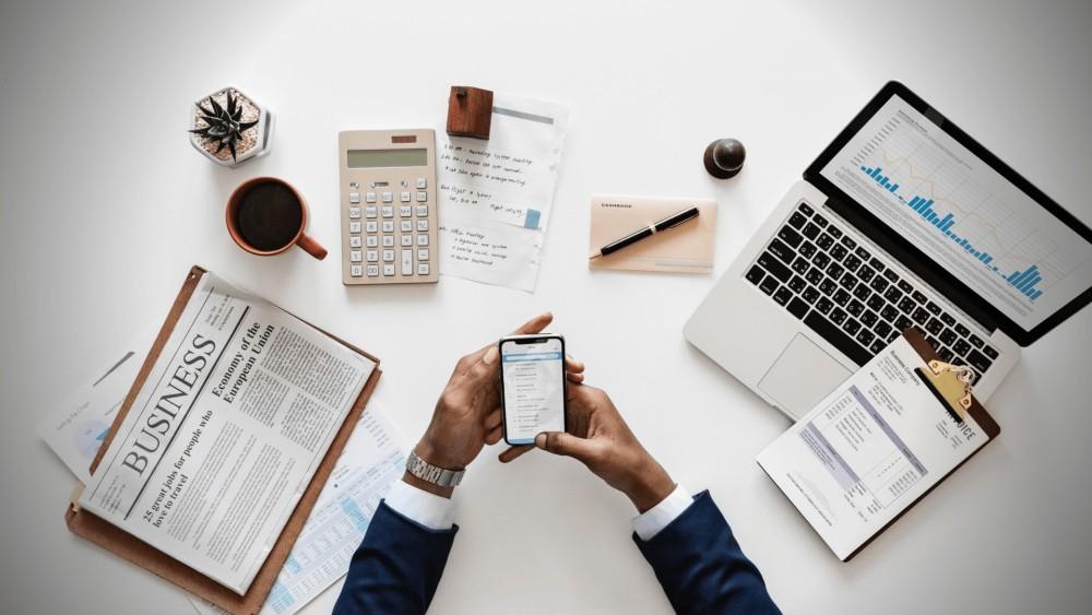 Een businessman in donkerblauwe blazer, met smartphone in de hand aan een witte bureautafel, met daarop een lichtgrijze laptop met financiële cijfers voor het financieel plan, business news, planten en andere accessoires.