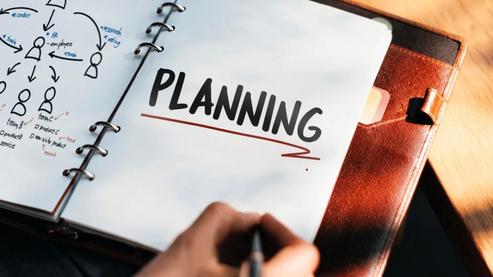 Persoon houdt zwarte balpen vast aan houten bureautafel met daarop een bruine leren map met papieren voor een goede planning voor een bedrijf.