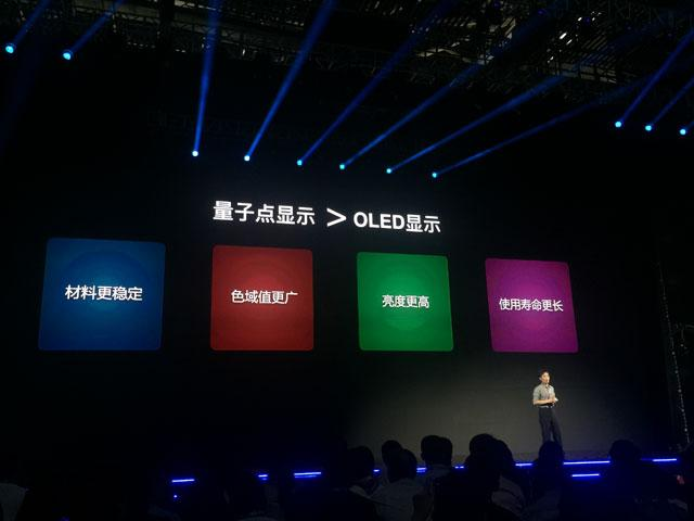 In case you can't read Chinese, the slide behind CTO Chen says: Quantum Dot Display > OLED Display and, from left to right, the four colored blocks: Materials More Stable/ Color Gamut Wider/ Brightness Higher/ Lifetime Longer