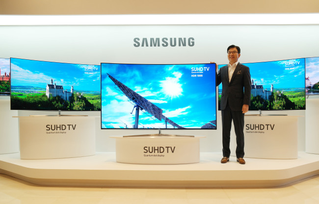 Samsung Electronics president and TV chief Kim Hyun-seok poses with the company's latest quantum dot TVs at a launch event in Seoul on Tuesday. (Samsung Electronics)