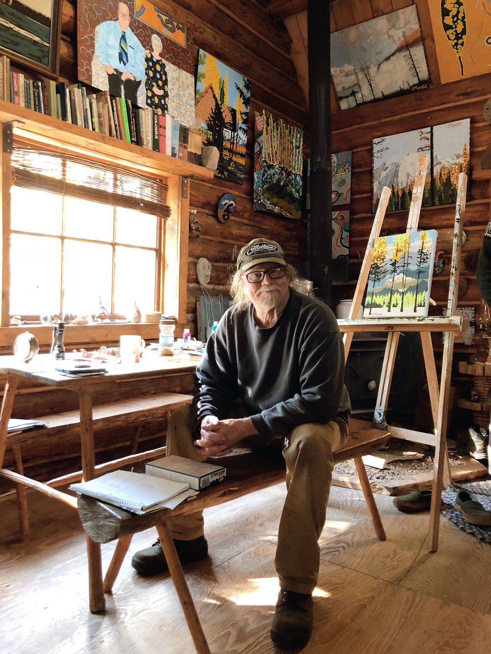 Peter Moore, Artist, sits comfortably at his easel.