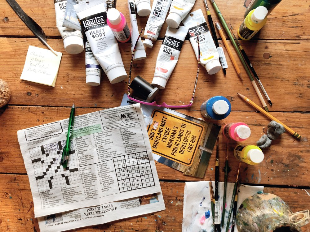Paints, brushes, and a crossword on the table.
