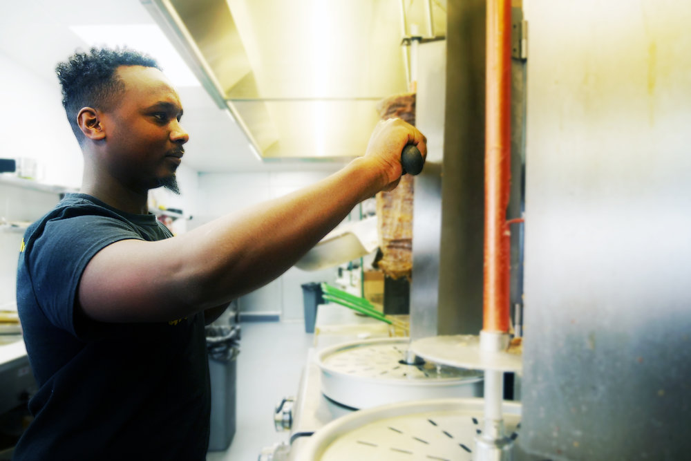 Abdi Ali works the deli counter in Karibu