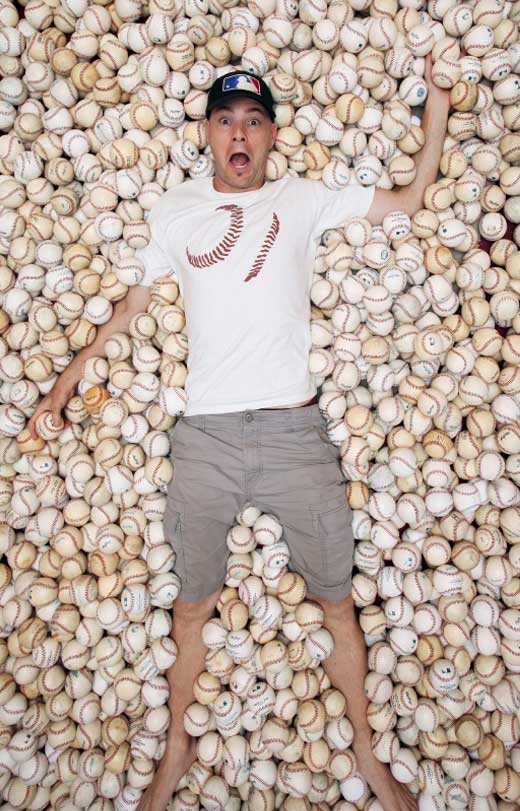 surrounded by baseballs for a photo shoot