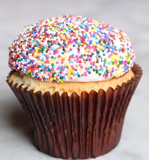 Vanilla cake with buttercream frosting topped with sprinkles.