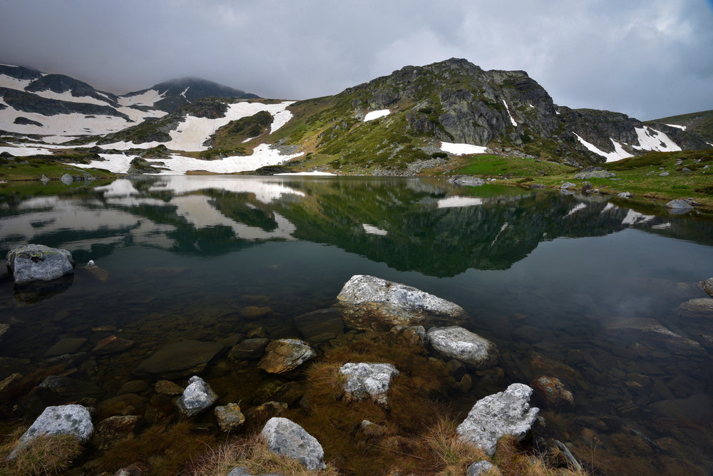 rila-mountain-lake-reflection-sprintime-snow-rocks-foreground-clouds-bulgaria-phototours-phil-2018-4118.jpg