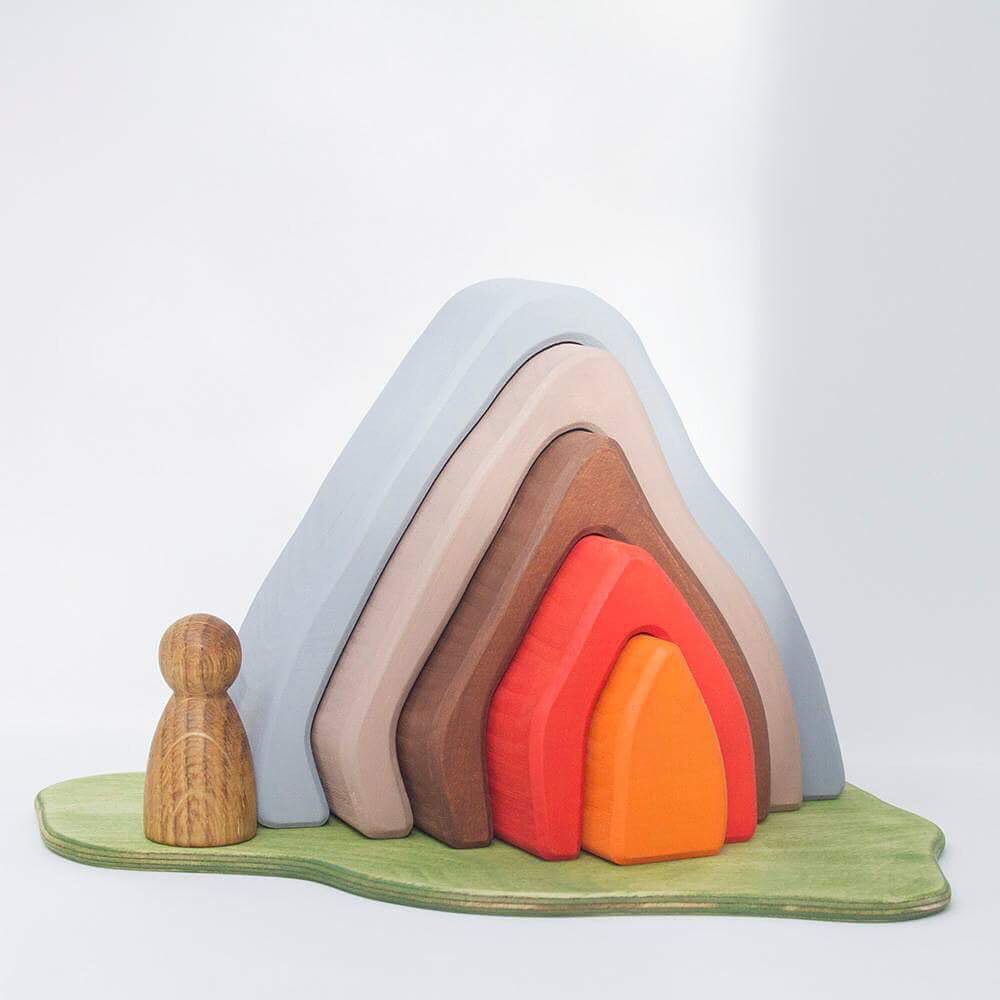 The Volcano   Bring your dinosaur collection alive or create railway bridges, houses and campfires. How many ways can you play?  Lime wood Play Scene cut from a single block of FSC kiln dried lime wood. Stained with water based, non-toxic colour and with a slightly textured surface.  Approximately 180mm x 150mm x 54mm RRP £33
