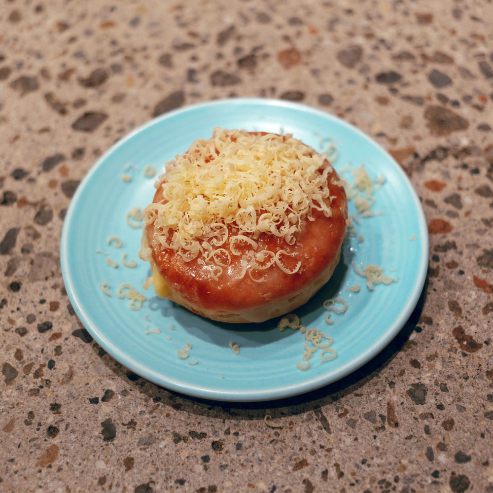 A generous garnish of freshly grated Comté to finish the donut.