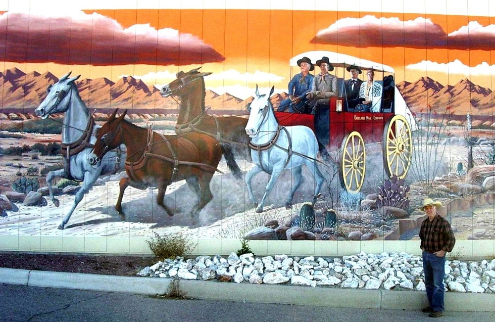 For the first time in Benson an accurate representation of one of John Butterfield's stage (celerity) wagons can be seen. He didn't use stagecoaches, as he needed a lighter stage for the rough environment of the southwest deserts. Almost all the stage drivers were from Upstate New York. The mural is on the Cochise County Regional Services Center in Benson. Gerald T. Ahnert (shown) is a historian, whose specialty is the Butterfield Trail in Arizona,  directed artist Doug Quarles for historical accuracy.