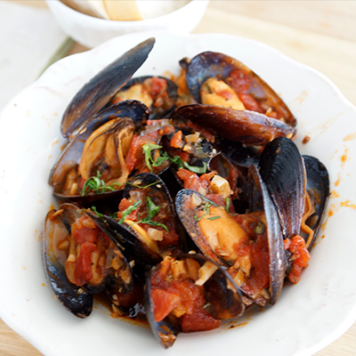 MUSSELS IN WHITE WINE & TOMATO SAUCE  Mussels are easy to dress up to look a million bucks. Using frozen prepackaged mussels meals (tomato or white wine varieties) eliminates cleaning, scrubbing and de-bearding.