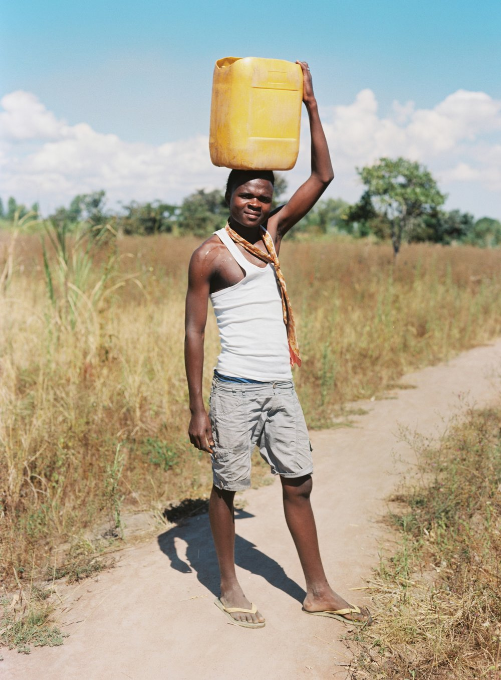 A young man on his way to collect water. Seleman II Village.