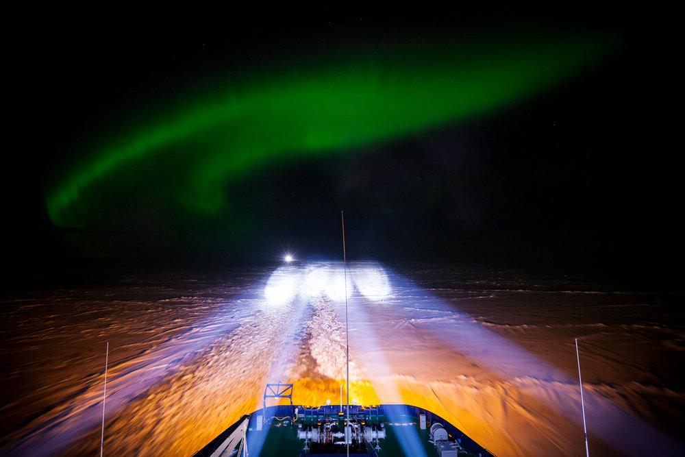 Norrskenet spelar över det istäckta havet när IB Oden är på väg mot ett rendevous.