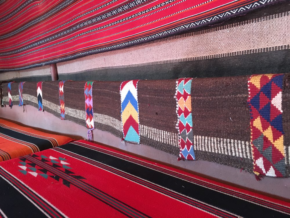 The interior of a communal Bedouin goat hair tent. The rugs here are similar to the ones seen on camels.