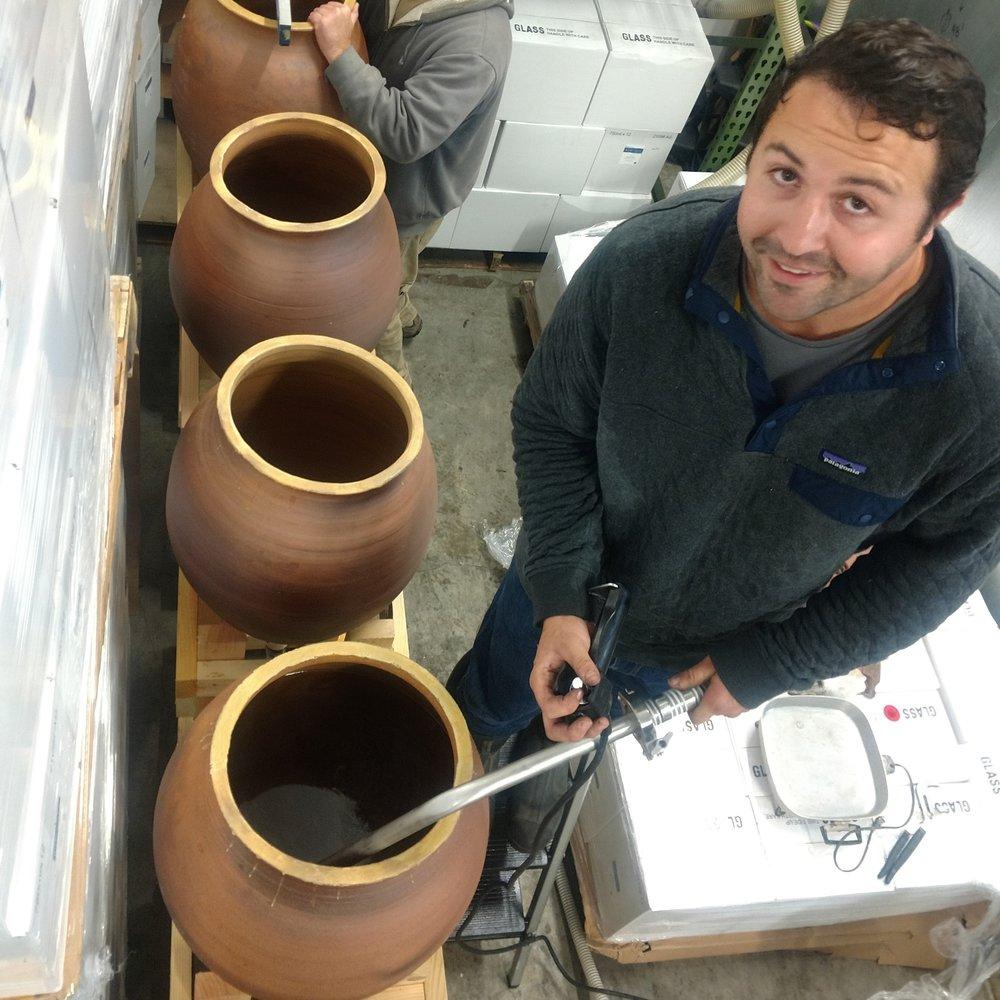 Tyler Bradley filling clay fermentation vessels with wine