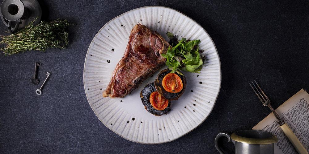 The Grahamston I Hand Cut 280g Ribeye Steak served with confit plum tomato, garlic flat cap mushroom & watercress.