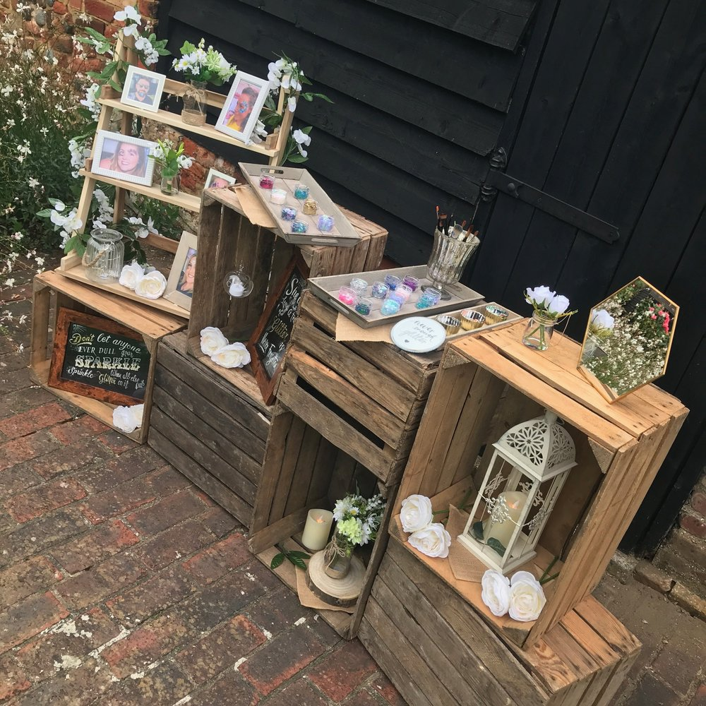THE RUSTIC BAR - This is built out of genuine apple crates, stacked and decorated with lanterns, flowers, candles and more, we place our glitter on the top and work from this.We suggest this is great for Weddings and boho themed events.