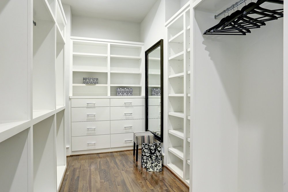 Spacious master closet with custom built cabinets & shelving.jpg