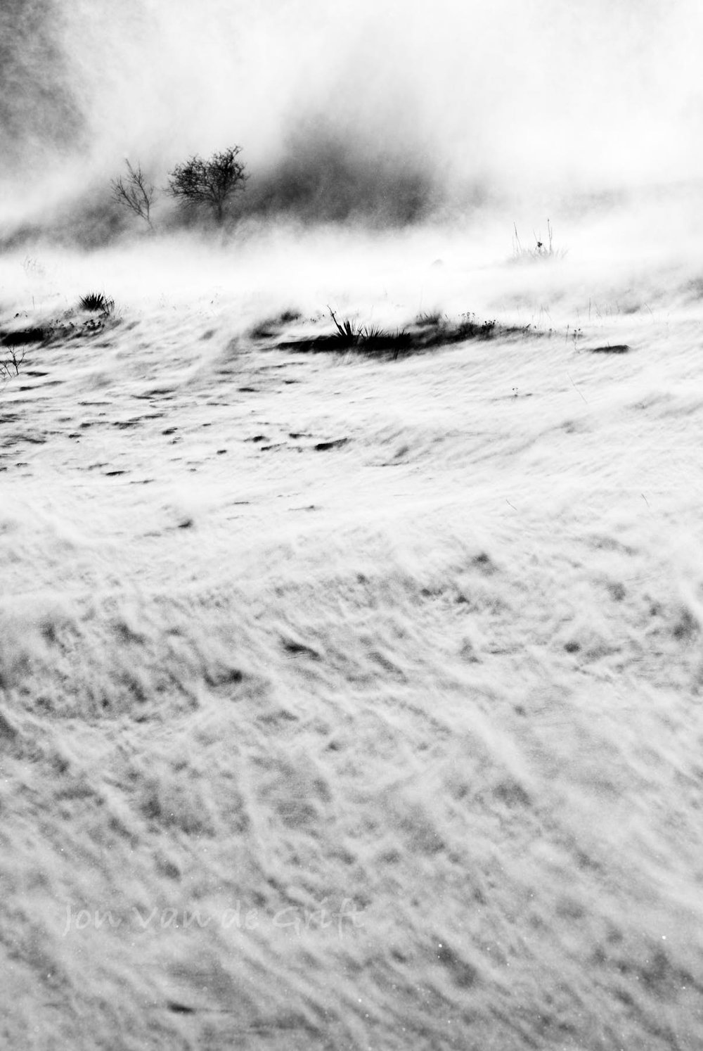 Black and white photograph of snow in a ground blizzard during winter.