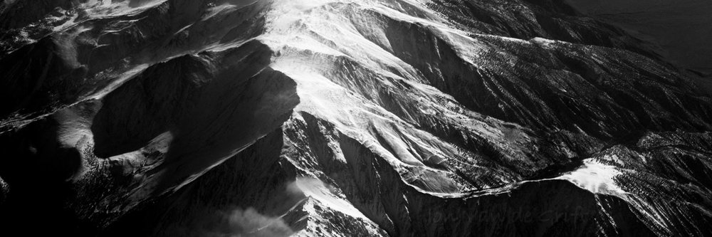 Monochrome aerial photography of snow on mountain summits.