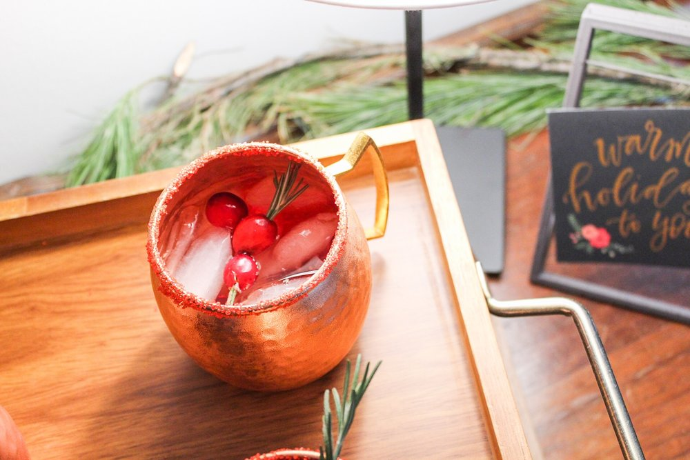 Cranberry moscow mule: 4 oz cranberry juice, 4 oz ginger beer, 2 oz vodka, squeeze of lime. I did the same rim coating and cranberry rosemary decor from morning mimosas above.