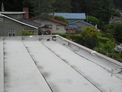 Before   Above is a picture of the torchdown roof that was installed two weeks before this picture was taken. The roof system was failing and needed to be replaced. You can see in the top right hand corner that the workmanship and application was done poorly.