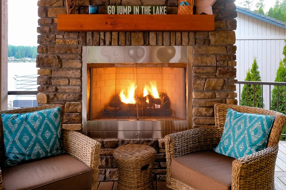 Covered & Cozy Outside Propane Fireplace with Flush Stone Face & Wood Mantle