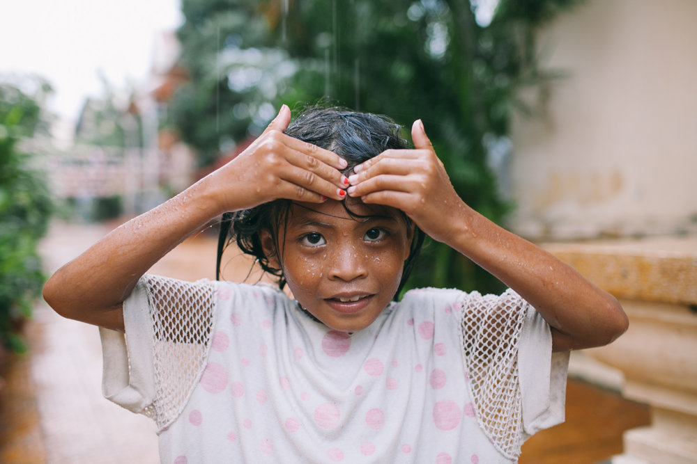 A girl poses for a portrait during a monsoon shower in Phnom Penh, Cambodia.