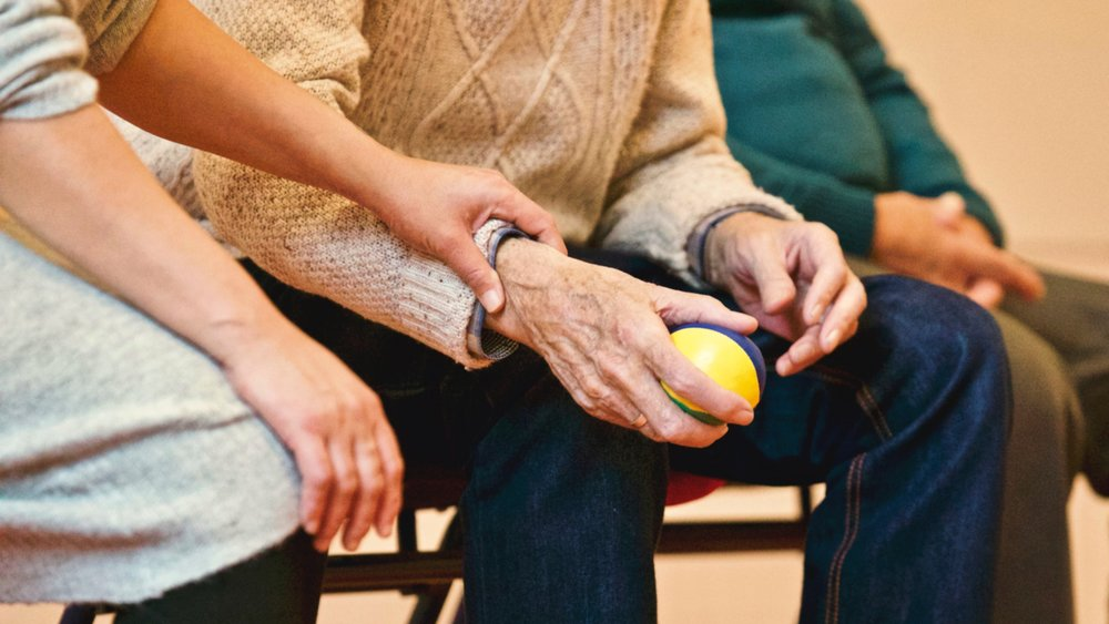 Elderly man holding a therapy ball, encouraged by a younger person's hand
