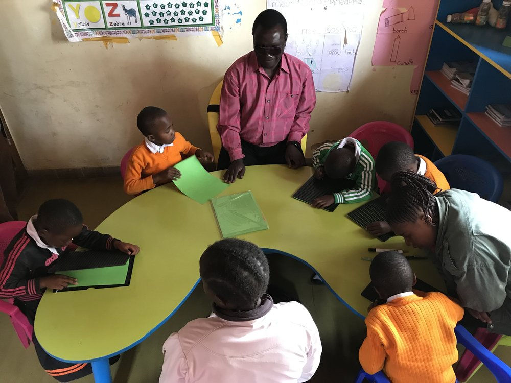 Children being taught braille by two visually impaired teachers at the existing school