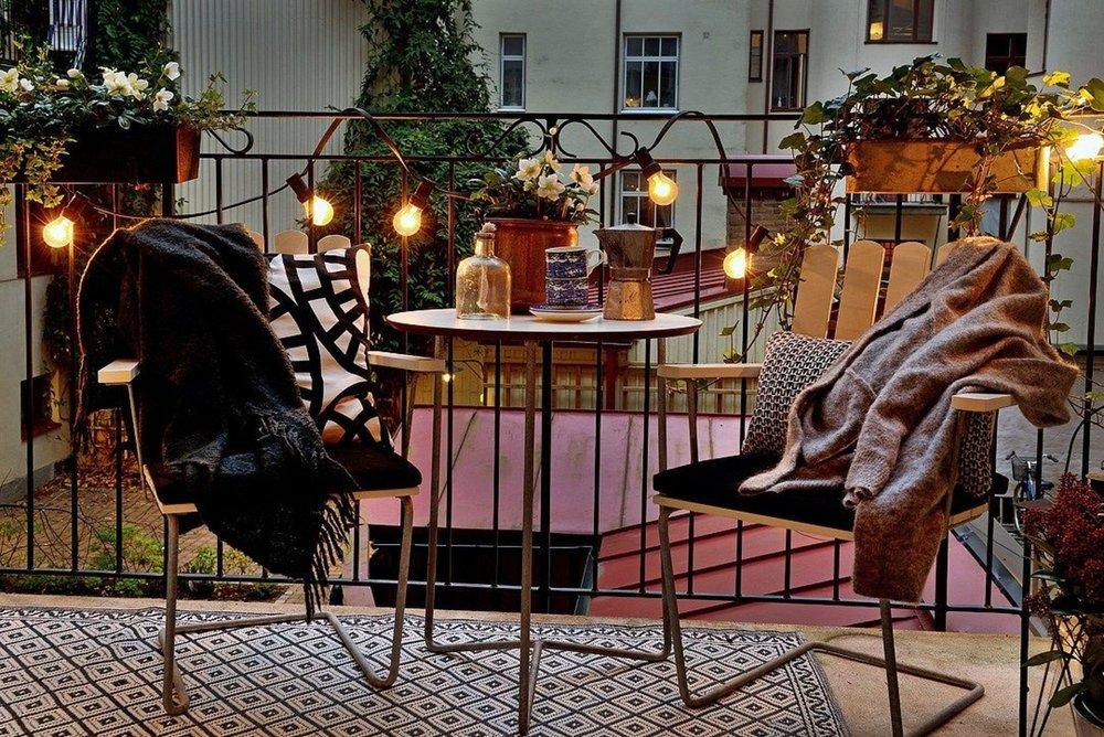 guirlande-lumineuse-sur-balcon-chaises-en-cuir-et-table-d-appoint_5891155.jpg