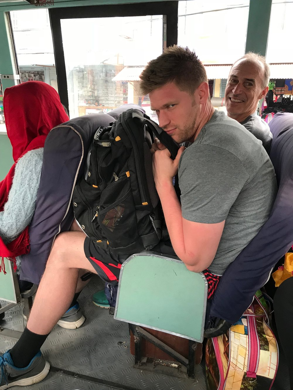 "Chris's 6'4"" frame in a bus seat"