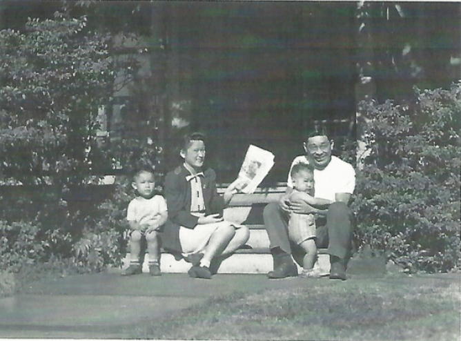 Original caption: Mr. and Mrs. George Nobori, formerly of the Jerome Relocation Center, now living in Cleveland where Nobori is employed as a machinist. They are seen with their two children on the porch of a house they have rented in a residential section of the city. Photographer: Charles E. Mace