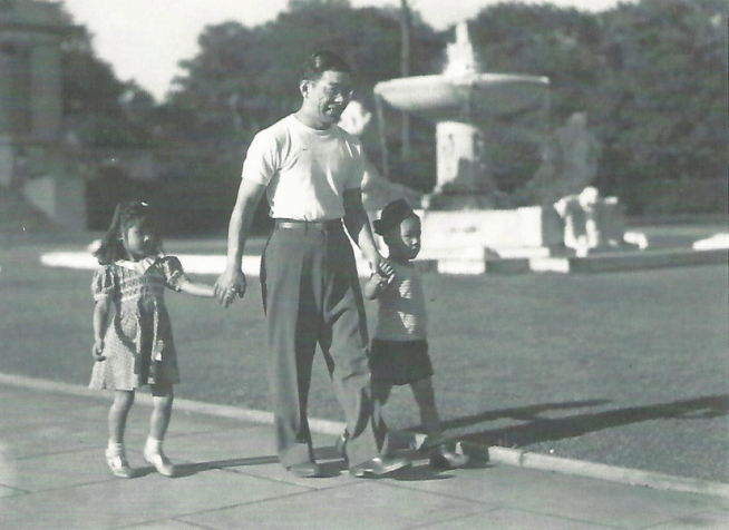 Original caption: George Nobori until six months ago was an evacuee in the Jerome Relocation Center, but is now a resident of Cleveland where he lives in comfortable quarters with his wife and children. He is employed as a machinist. Nobori is shown walking in a Cleveland park with his son George Jr. and playmate Marilyn Takeshima. Photographer: Charles E. Mace
