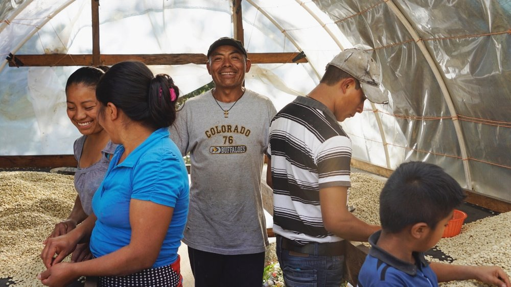 Producer Porfirio Lopez with his family in their solar dryer.
