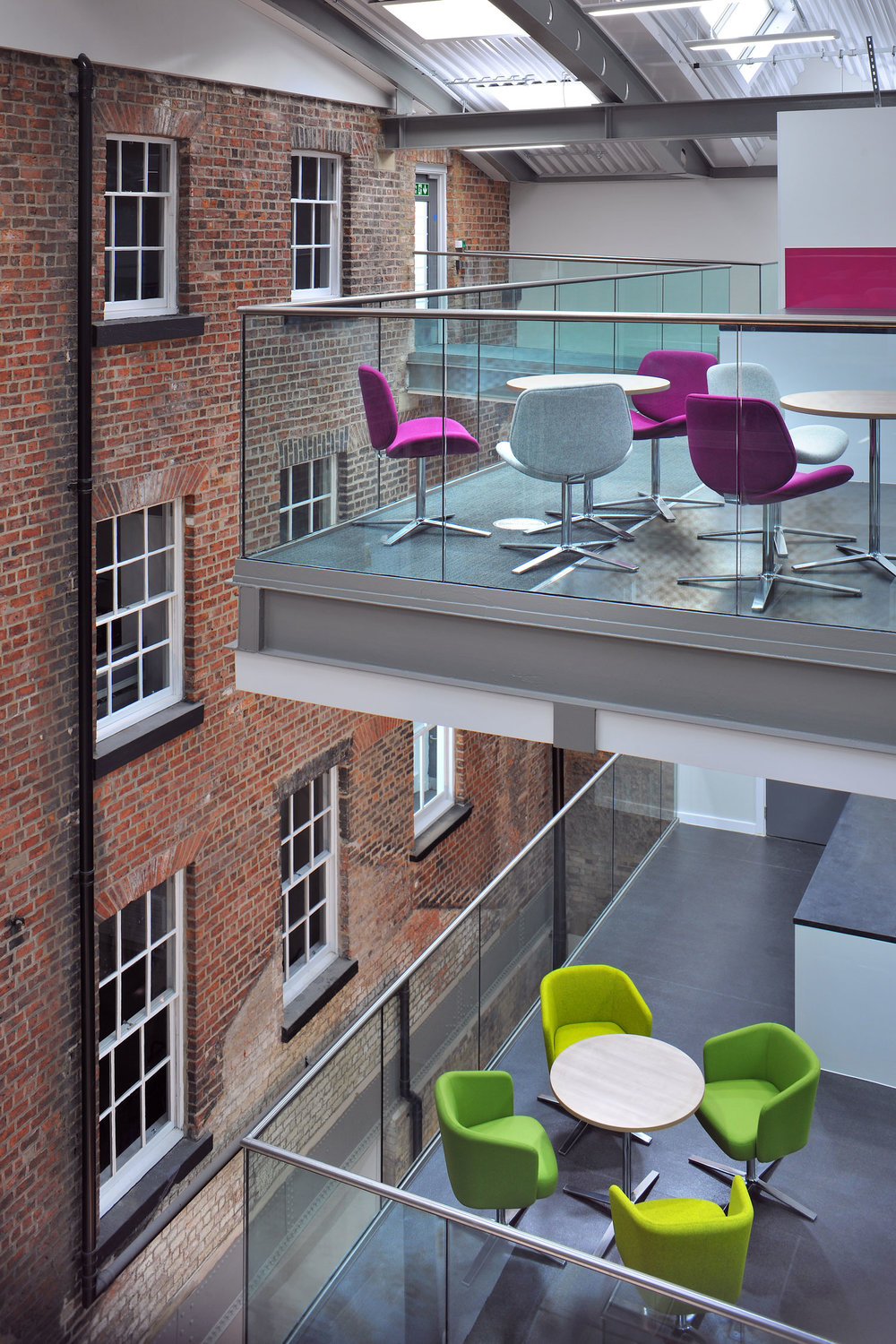 Purple, white and green office furniture with brickwork wall