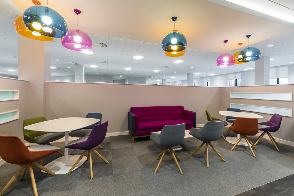 Breakout area with red, blue, green and purple seating and lighting