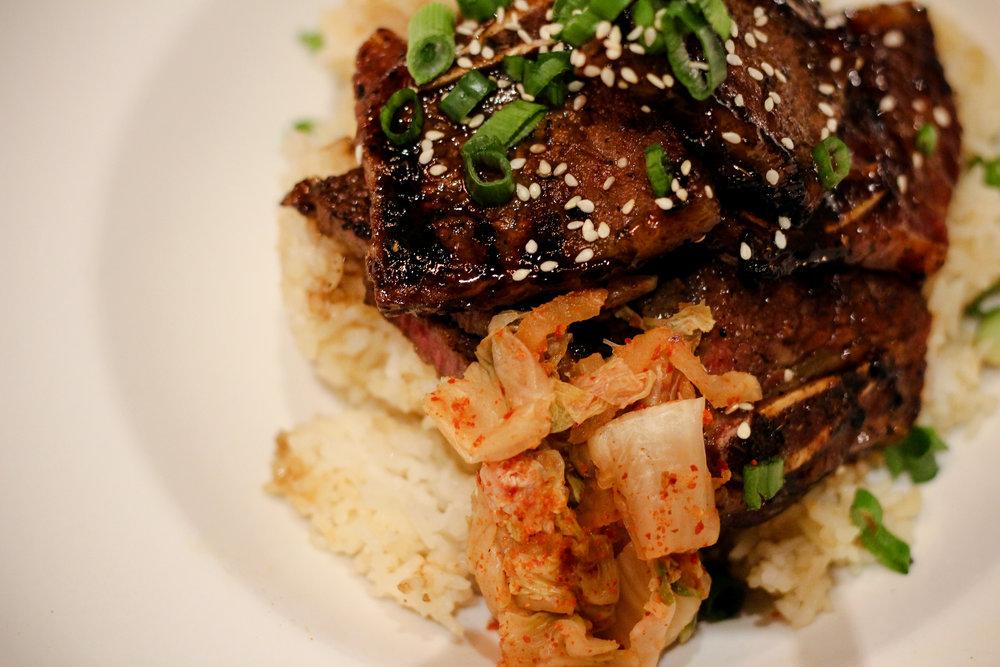 Korean Style Short Ribs Served over garlic rice with a side of fresh Kimchi