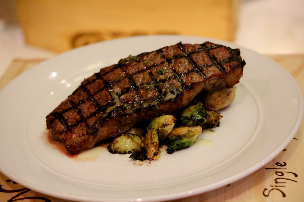 GRILLED NEW YORK STRIP STEAK ROSEMARY-ROASTED YUKON GOLD POTATO BALSAMIC-BRAISED BRUSSELS SPROUTS SAGE BUTTER