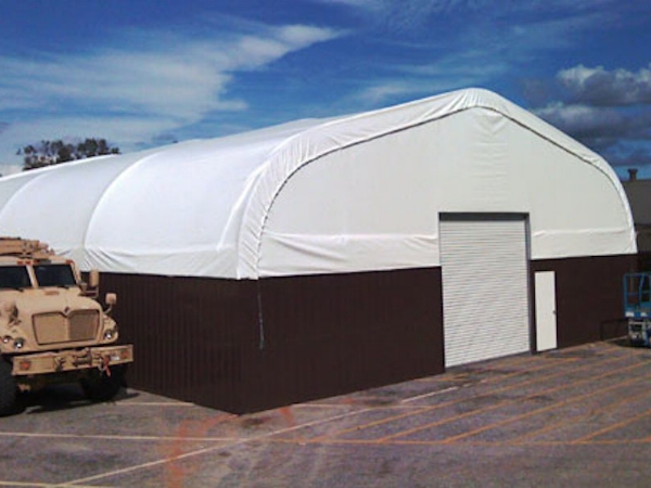 Shelter Structures completed a much sought after hybrid building. Designed at the request of the 75th Ranger Regiment at Ft. Benning, GA, this building includes a metal hard-side for added durability, and industrial composite flooring, extending the life of an old asphalt pad. Our standard 20oz translucent PVC fabric building roofing provides natural light, and this hybrid fabric structure building can be erected anywhere. Any height, any length, any width.