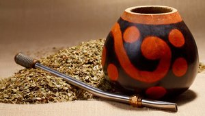 A traditional gourd vessel. Yerba mate tea is sipped through a metal straw.