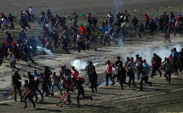 Migrants, including children, flee from tear gas used by US Customs and Border Protection agents at the border. REUTERS/Hannah McKay
