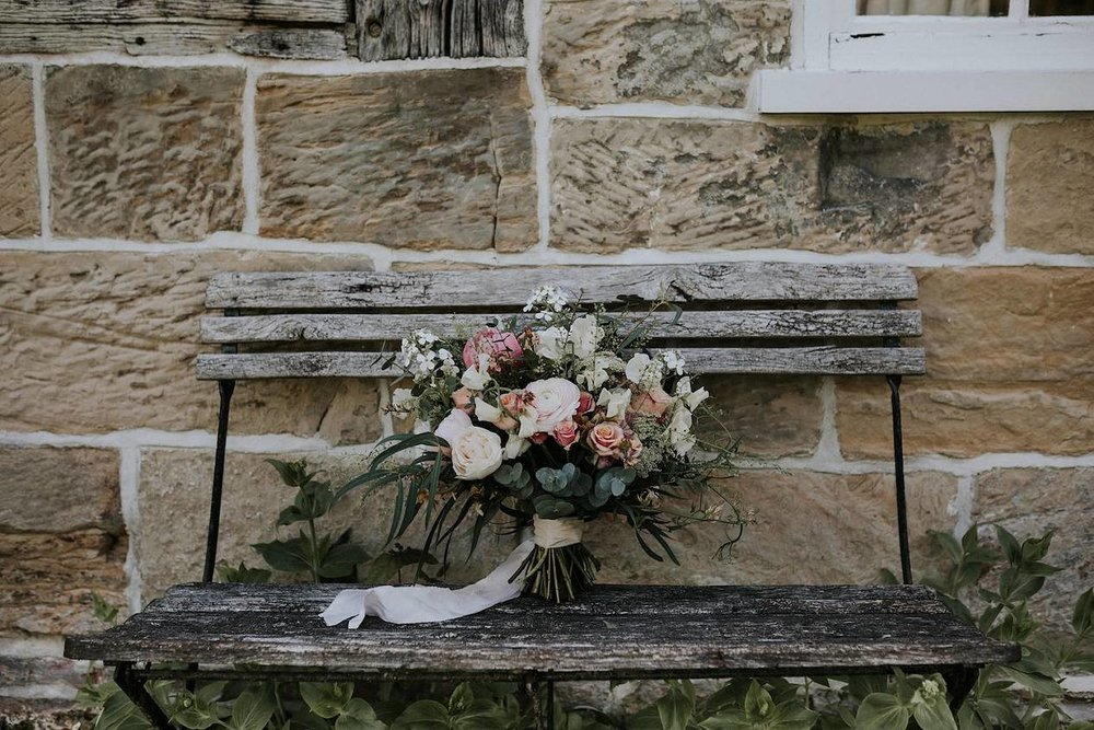 Pastel bridal bouquet on wooden bench