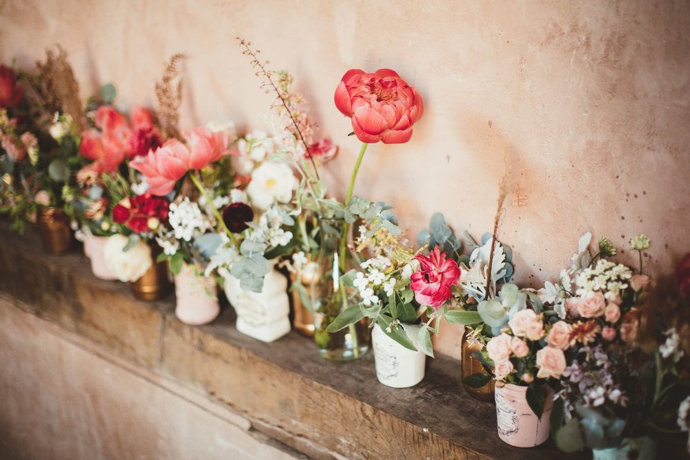 Coral and mint green flowers in jam jars on wooden shelf