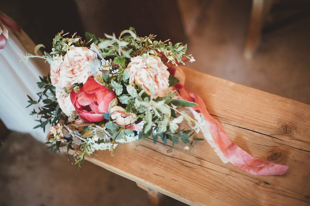 Bouquet with coral peony, pale pink roses, silk ribbon on registrar table