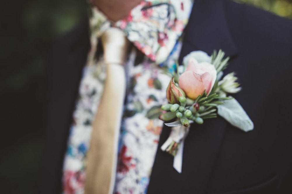 Groom buttonhole with pale pink rose and herbs