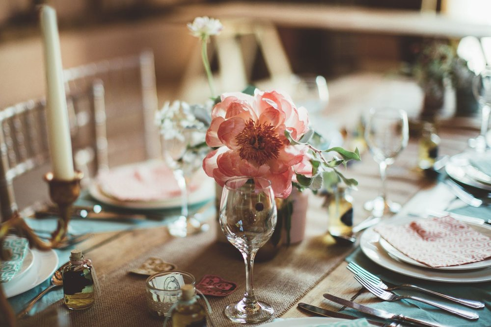 Peony, roses and herbs in jars on wedding table